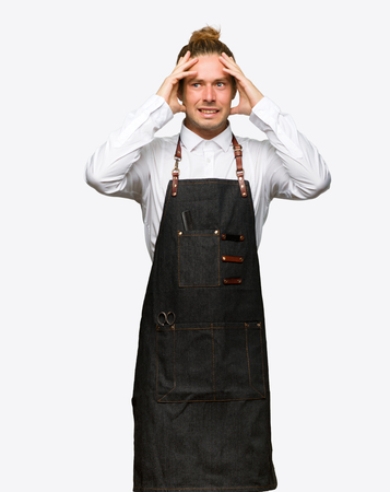 Barber man in an apron takes hands on head because has migraine on isolated background Foto de archivo