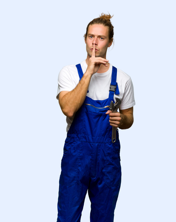 Workman showing a sign of silence gesture putting finger in mouth on isolated background