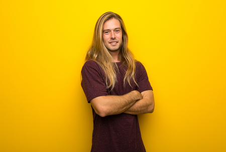 Blond man with long hair over yellow wall keeping the arms crossed in frontal position