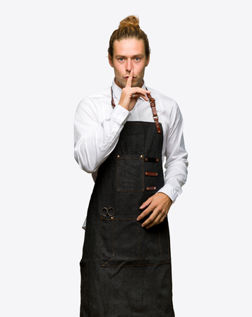 Barber man in an apron showing a sign of silence gesture putting finger in mouth on isolated background