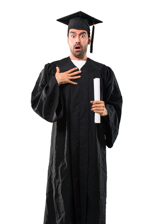 Man on his graduation day University surprised and shocked while looking right. Expressive facial emotion