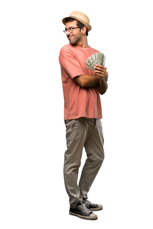Man holding many bills looking over the shoulder with a smile on isolated white background