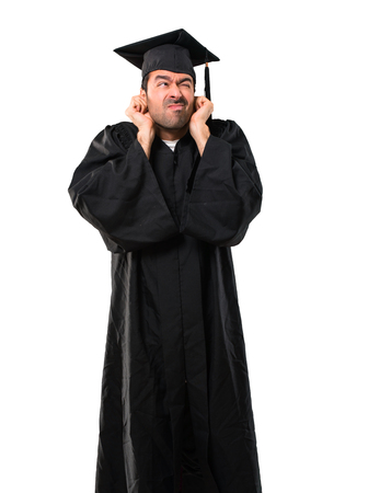 Man on his graduation day University covering both ears with hands. Frustrated expression on isolated white background Stock Photo
