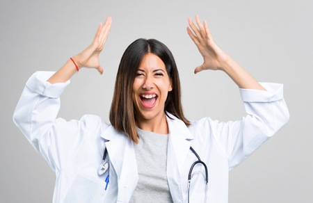 Doctor woman with stethoscope with surprise and shocked facial expression. Gaping because can not believe what is happening on grey background Stok Fotoğraf