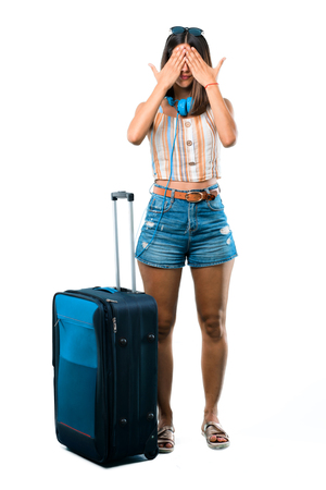Full body of Girl traveling with her suitcase covering eyes by hands. Do not want to see something on isolated white background