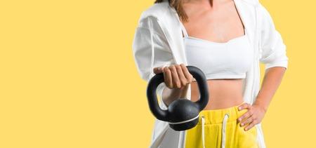 Sport woman with kettlebell on yellow background Reklamní fotografie