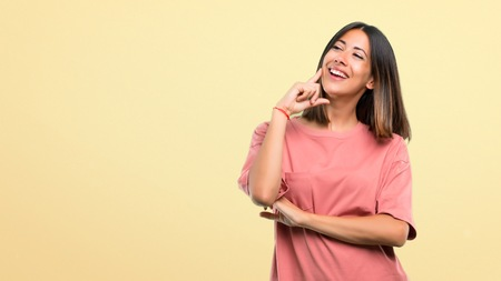 Young girl with pink shirt standing and thinking an idea while looking up on yellow background 免版税图像