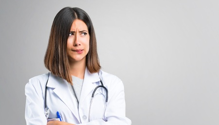 Doctor woman with stethoscope having doubts and with confuse face expression while bites lip. Questioning an idea on grey background Stock Photo
