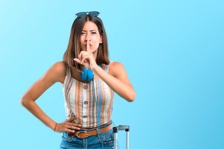Girl traveling with her suitcase showing a sign of closing mouth and silence gesture putting finger in mouth on blue background Standard-Bild