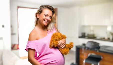 Pregnant woman in pajamas with stuffed animal at home