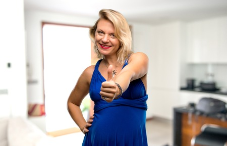 Pregnant blonde woman with blue dress giving a thumbs up gesture and smiling in her house