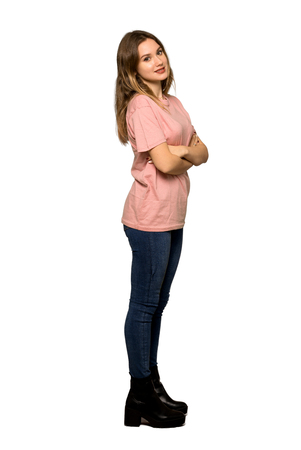 A full-length shot of a Teenager girl with pink sweater with arms crossed and looking forward on isolated white background 版權商用圖片