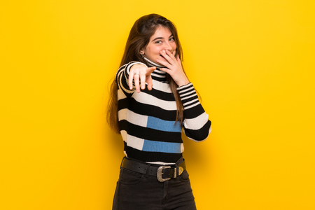 Young woman over yellow wall pointing with finger at someone and laughing Stockfoto