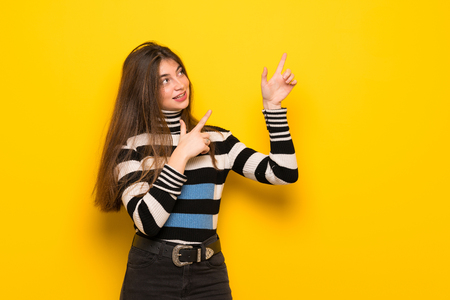 Young woman over yellow wall pointing with the index finger and looking up