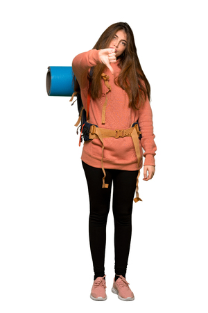 Full-length shot of Hiker girl showing thumb down sign with negative expression on isolated white background