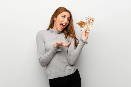 Redhead girl over white wall taking a lot of money