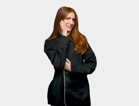 Young redhead chef woman with toothache on isolated grey background Imagens
