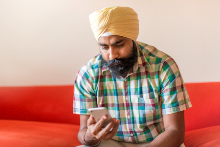 Indian with turban using mobile phone Banque d'images