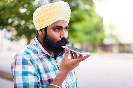 Indian with turban using mobile phone in outdoors