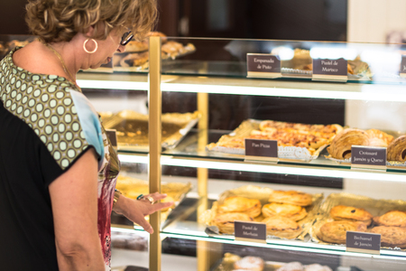 Customer looking at cakes in a bakery to buy Banco de Imagens