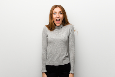 Redhead girl over white wall with surprise and shocked facial expression Stok Fotoğraf