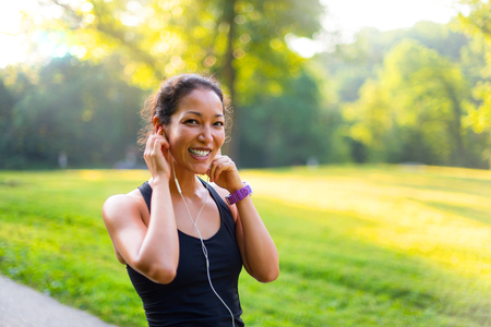 Sport asian woman listening to music with headphones outdoors