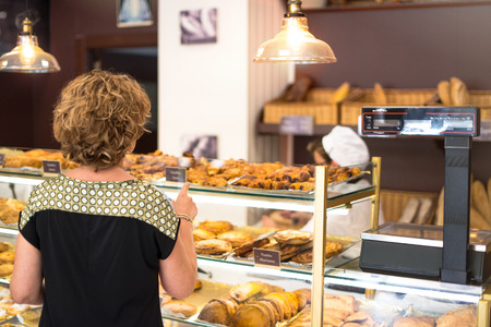 Woman pointing with a finger at a dumpling she wants to buy in a bakery Banco de Imagens
