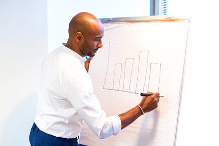 Young afro american businessman in the office writing on whiteboard a planning strategy Banque d'images