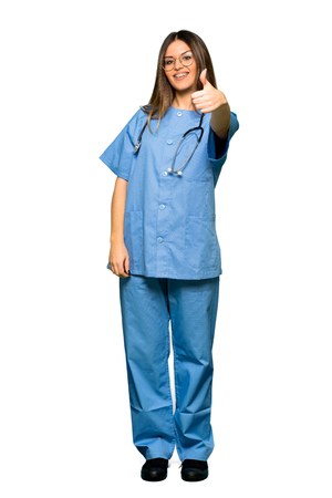 Full body of Young nurse giving a thumbs up gesture because something good has happened