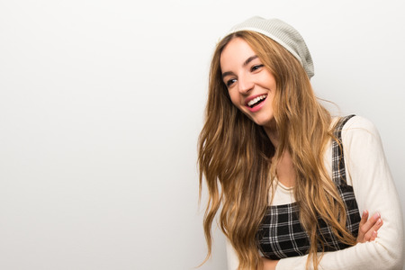 Fashionably woman wearing hat keeping the arms crossed while smiling