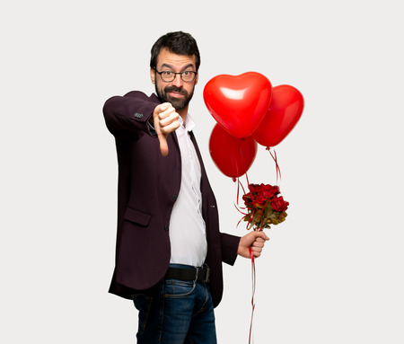 Man in valentine day showing thumb down sign with negative expression over isolated grey background 写真素材 - 115784828