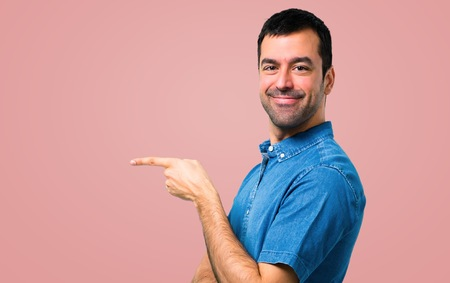 Handsome man with blue shirt pointing finger to the side and presenting a product on pink background Фото со стока