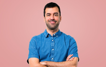 Handsome man with blue shirt keeping arms crossed on pink background