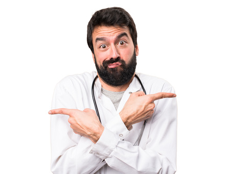Young doctor pointing to the laterals having doubts on white background