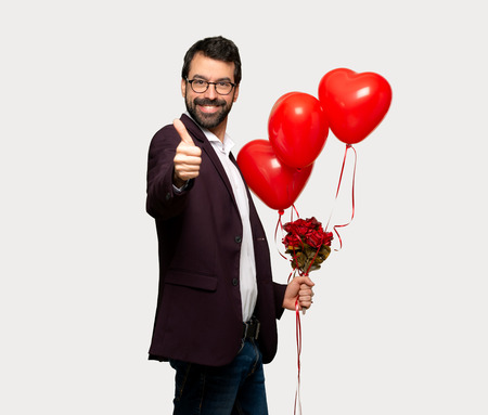 Man in valentine day giving a thumbs up gesture because something good has happened over isolated grey background