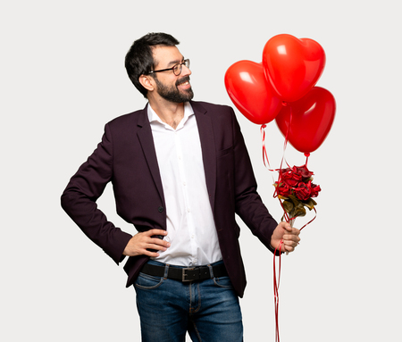 Man in valentine day posing with arms at hip and laughing over isolated grey background