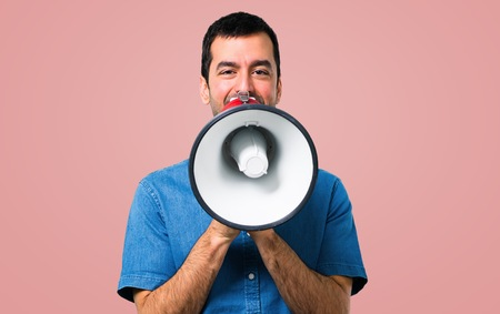 Handsome man with blue shirt holding a megaphone on pink background