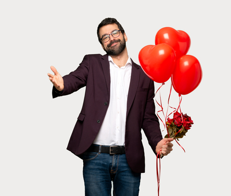 Man in valentine day presenting and inviting to come with hand over isolated grey background Standard-Bild