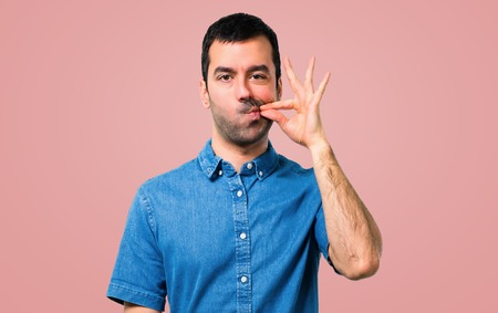 Handsome man with blue shirt showing a sign of closing mouth and silence gesture on pink background