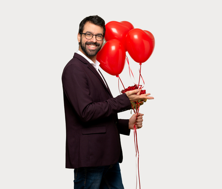 Man in valentine day presenting an idea while looking smiling towards over isolated grey background