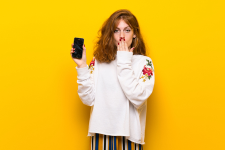 Young redhead woman over yellow wall with troubled holding broken smartphone