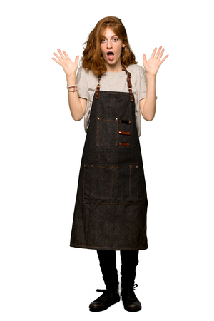 A full-length shot of a Young redhead woman with apron with surprise and shocked facial expression over isolated white background