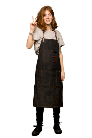A full-length shot of a Young redhead woman with apron intending to realizes the solution while lifting a finger up over isolated white background
