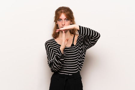 Young redhead woman over white wall making stop gesture with her hand to stop an act