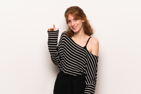 Young redhead woman over white wall saluting with hand with happy expression Archivio Fotografico