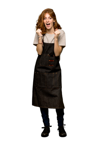 A full-length shot of a Young redhead woman with apron celebrating a victory in winner position over isolated white background
