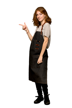 A full-length shot of a Young redhead woman with apron pointing finger to the side in lateral position over isolated white background