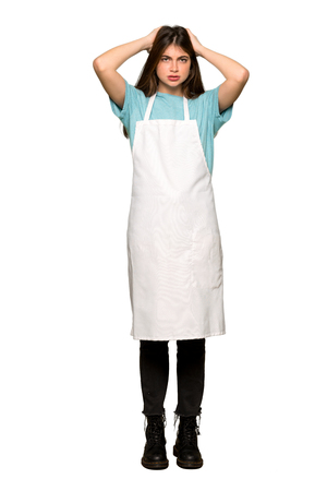 Full-length shot of Girl with apron takes hands on head because has migraine on isolated white background
