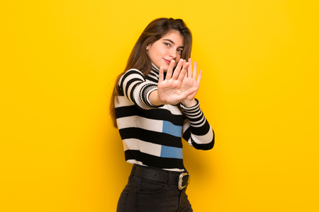 Young woman over yellow wall is a little bit nervous and scared stretching hands to the front