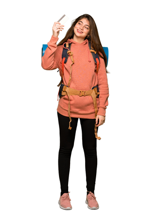 Full-length shot of Hiker girl holding a credit card and thinking on isolated white background